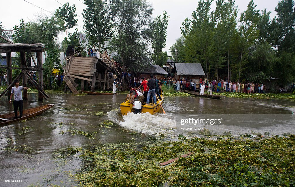 Volunteers and rescuers search for survivors in the water after a footbridge collapsed into the water on August 11, 2012 in Srinagar, the summer capital of Indian administered Kashmir, India. According to witnesses and locals many people were injured some of them critically after an old makeshift foot bridge partially crumbled down due to overweight, in the interiors of Dal Lake .