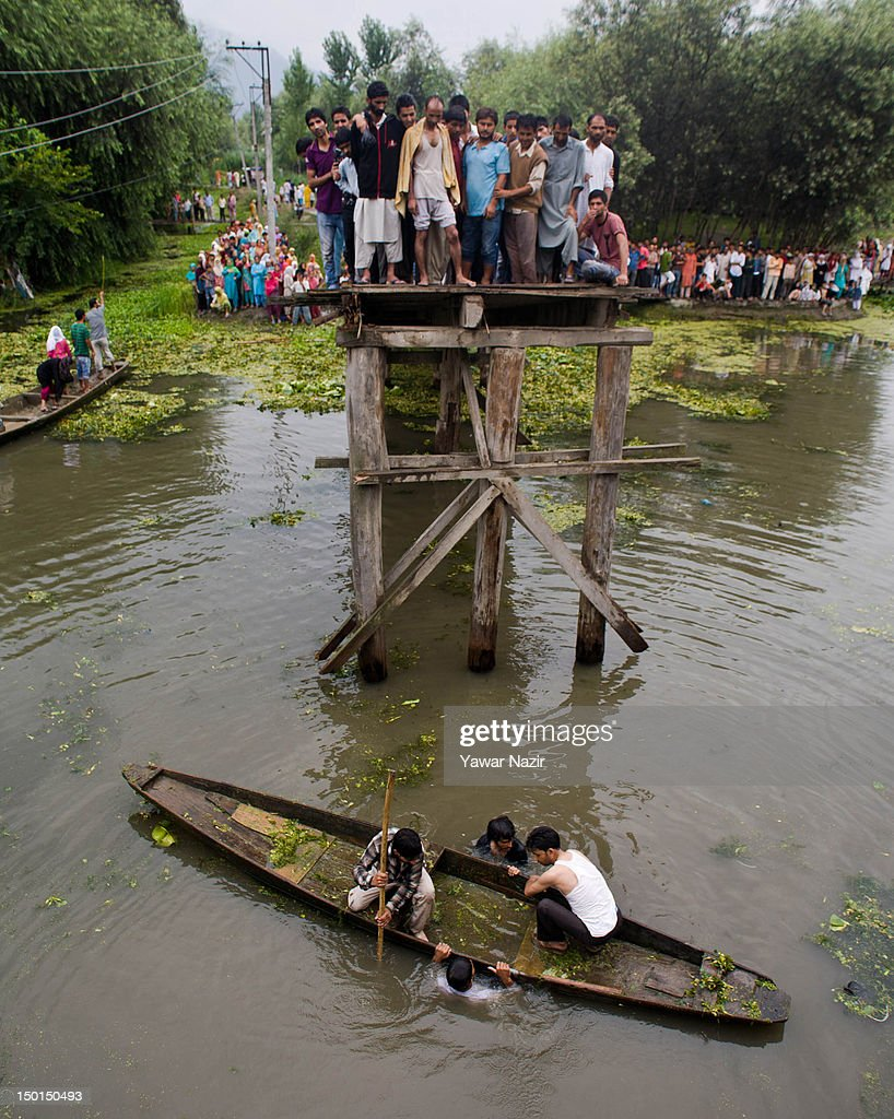 Volunteers and rescuers search for survivors in the water after a footbridge collapsed into the water of on August 11, 2012 in Srinagar, the summer capital of Indian administered Kashmir, India. According to witnesses and locals many people were injured some of them critically after an old makeshift foot bridge partially crumbled down due to overweight, in the interiors of Dal Lake .