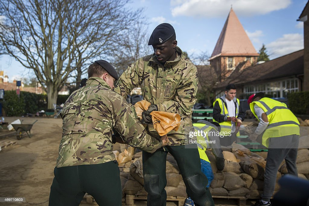 Volunteers and soldiers from the 1st Regiment Royal Horse Artillery load sandbags into military vehicles outside The Magna Carter school on February 16 2014 in Staines, England. Housing near the river Thames has suffered a week of flooding after the river burst its banks on February 10, 2014.