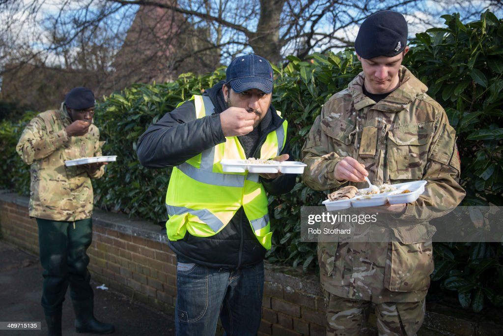 Volunteers and soldiers from the 1st Regiment Royal Horse Artillery eat a meal provided by Gurudwara Sri Guru Singh Sabha, a Sikh Gurdwara situated in the London suburb of Southall, outside The Magna Carter school on February 16 2014 in Staines, England. Housing near the river Thames has suffered a week of flooding after the river burst it's banks on February 10, 2014.