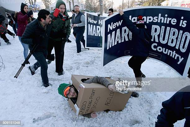 Volunteers and staff for Republican presidential candidate Sen Marco Rubio run past trackers and demonstrators including Eddie Vale of American...