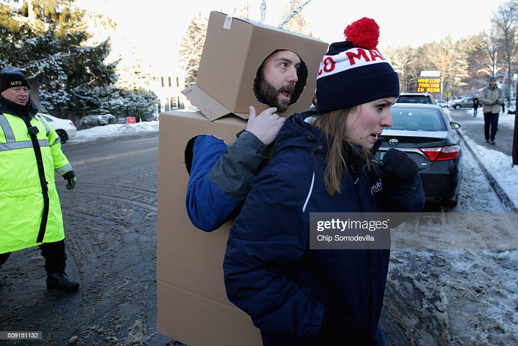 Volunteers and staff for Republican presidential candidate Sen. Marco Rubio (R-FL) with trackers and demonstrators, including Kevin McAlister of the American Bridge 21st Century political action committee dressed as a robot, pushed, shoved and wrestled as Rubio stopped to thank supporters outside the polling place at Webster School February 9, 2016 in Manchester, New Hampshire. With a good showing in the Iowa caucuses, Rubio has stepped into the crosshairs of fellow Republicans running for president and super PACs that want to slow his momentum with attacks on what they call his robotic and repetative messaging.