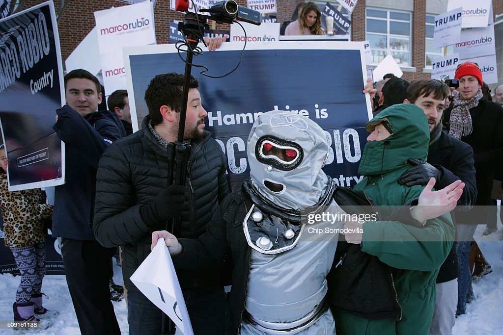 Volunteers and staff for Republican presidential candidate Sen. Marco Rubio (R-FL) and trackers and demonstrators dressed as robots from the American Bridge 21st Century political action committee pushed, shoved and wrestled as Rubio stopped to thank supporters outside the polling place outside Webster School February 9, 2016 in Manchester, New Hampshire. With a good showing in the Iowa caucuses, Rubio has stepped into the crosshairs of fellow Republicans running for president and super PACs that want to slow his momentum with attacks on what they call his robotic and repetative messaging.