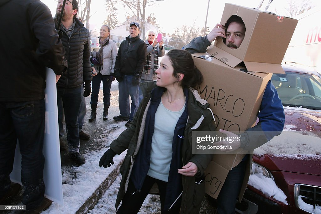 Volunteers and staff for Republican presidential candidate Sen. Marco Rubio (R-FL) trackers and demonstrators, including Kevin McAlister of the American Bridge 21st Century political action committee dressed as a robot, pushed, shoved and wrestled as Rubio stopped to thank supporters outside the polling place at Webster School February 9, 2016 in Manchester, New Hampshire. With a good showing in the Iowa caucuses, Rubio has stepped into the crosshairs of fellow Republicans running for president and super PACs that want to slow his momentum with attacks on what they call his robotic and repetative messaging.