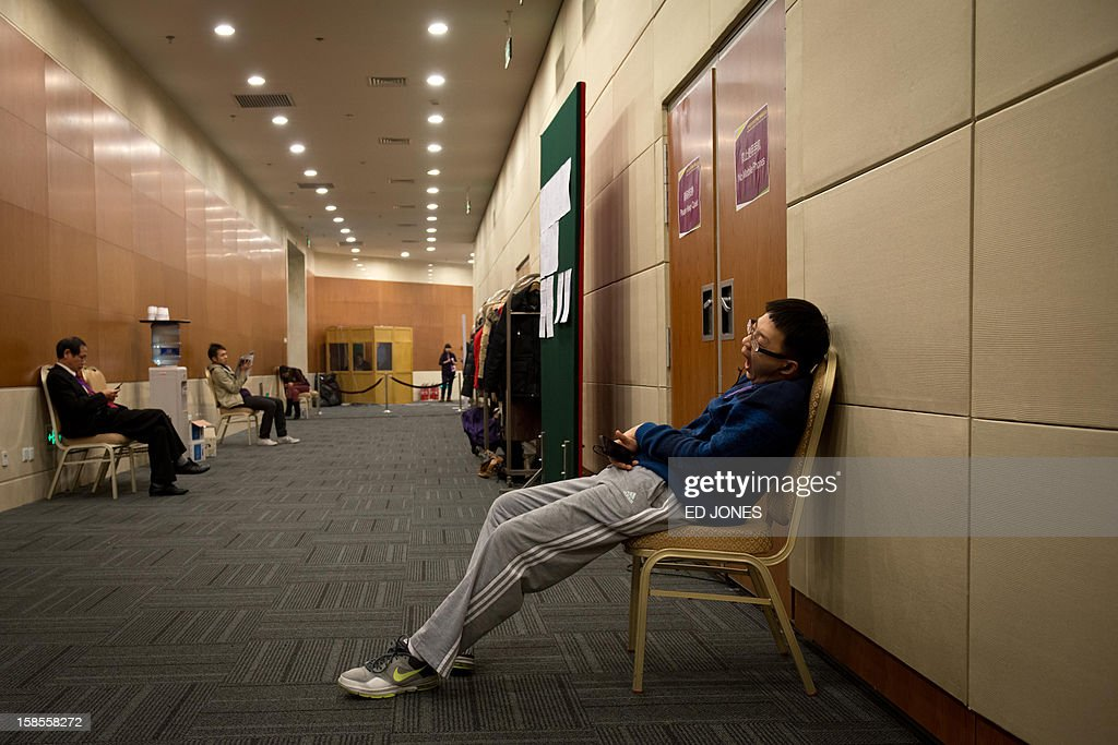 Volunteers and staff rest outisde the venue of a 'blinfold' chess tournament at the Beijing 2012 World Mind Games Tournament in Beijing on December 19, 2012. Some of the world's top chess players went eye-to-eye in the year's highest-level 'blindfold' chess tournament -- seen by some as the toughest challenge in the game. Unable to physically see their own or their opponent's past moves, the players summoned headache-inducing levels of concentration to fight for gold in a silent conference room, lined up in front of laptop screens showing a blank board. AFP PHOTO / Ed Jones
