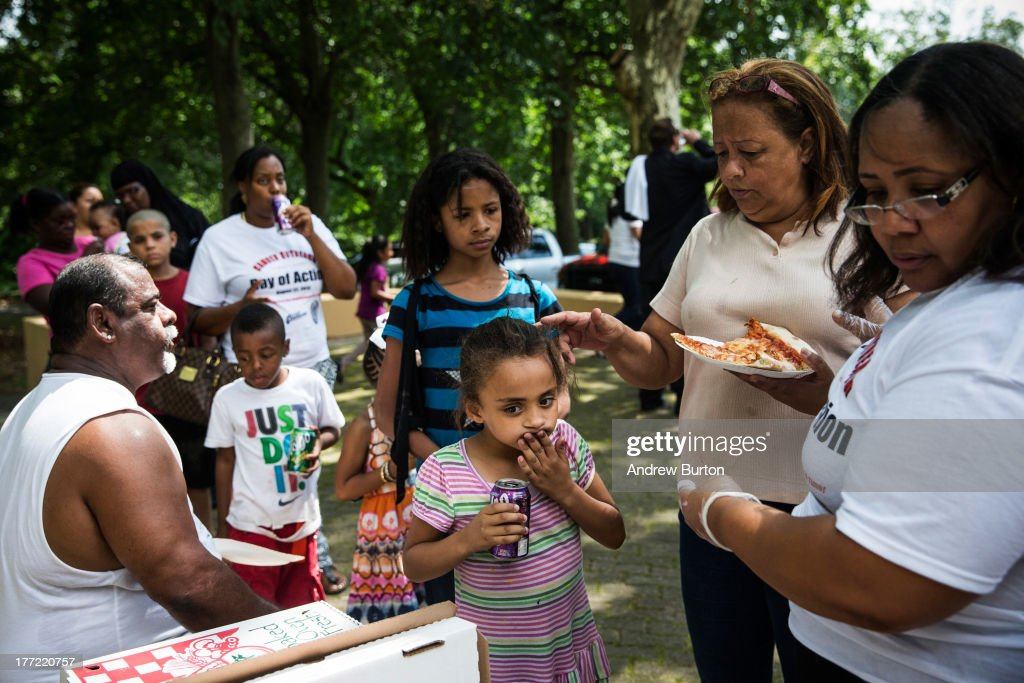 Volunteers are handed free pizza during a day of action, organized by Camden County Police Department (CCPD), on August 22, 2013 in the Parkside neighborhood of Camden, New Jersey. The day of action included the cleaning of Farnham Park and general neighborhood interaction between the CCPD, faith leaders and locals. The town of Camden, which was once a large industrial town but watched it's population dwindle as manufacturing left, has been marred with societal problems including high unemployment, crime, murder and heavy drug trafficking for decades. The Camden County Police Department was officially created in May, 2013, after the unionized Camden Police department was disbanded. The overhaul, which was supported by New Jersey Governor Chris Christie, has been considered unprecendented and has been closely watched around the country. The new force currently has approximately 280 members, and will reach full size by December, with 400 members. Early signs suggest the overhaul has been effective - The Wall Street Journal reported earlier this month that Camden murder rates fell 29% from May, 2013 to July 2013, compared to the same period last year. Absentee rates of the CCPD is also lower: approximately 5% of officers have been reported absent so far, compared to approxmiately 30% of the Camden Police Department prior to the change in command.