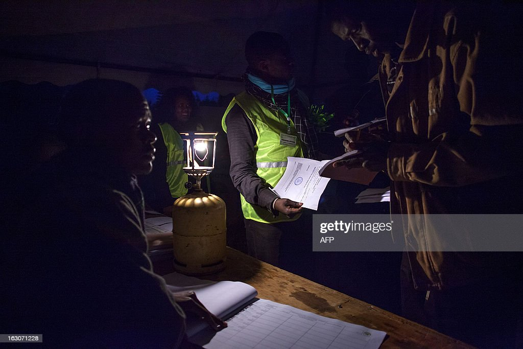 Volunteers at the Manyatta Primary School polling station in Langata, a suburb of Nairobi, prepare ballot papers by lamplight at dawn before voting opens on March 4, 2013 during the elections. Long lines of Kenyans queued from way before dawn to vote Monday in the first election since the violence-wracked polls five years ago, with a deadly police ambush hours before polling started marring the key ballot. The tense elections are seen as a crucial test for Kenya, with leaders vowing to avoid a repeat of the bloody 2007-8 post-poll violence in which over 1,100 people were killed and observers repeatedly warning of the risk of renewed conflict.