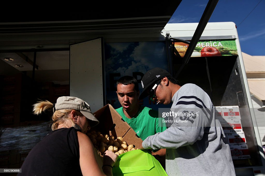 LR Volunteers Autumn McNew Shawn Macias and Edgar Ramirez pour Potatoes into a bag at a Feeding America truck on Thursday November 3 2011 in Descanso...