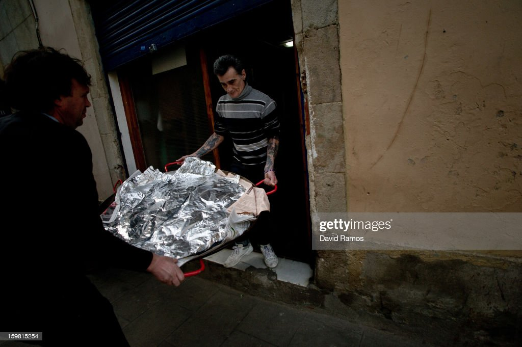 Volunteers bring in a paella, donated by a Michelin starred restaurant, for guests at the 'El Chiringuito de Dios' ('The Stall of God') on January 10, 2013 in Barcelona, Spain. The German pastor Wolfgang Striebinger has lived in Barcelona since 1991, originally employed to minister to youths during the Barcelona Olympic Games, he decided to stay and since 2000 has run 'El Chinguito de Dios' (The Stall of God). In his mission to support the homeless, Wolfgang and his volunteers offer a place for up to 200 people to come and have some food daily and also offering them assistance with grooming and clothes. Many of the volunteers are homeless and help out in return for meals and a bed. Wolfgang's ethos is to provide peace, calm and dignity to all those that need it amongst Barcelona's burgeoning homeless population. Due to the economic situation his doors are now also open to the long term unemployed and families with little or no income. According to the latest figures 21.8% of the Spanish populations are living below the poverty line.