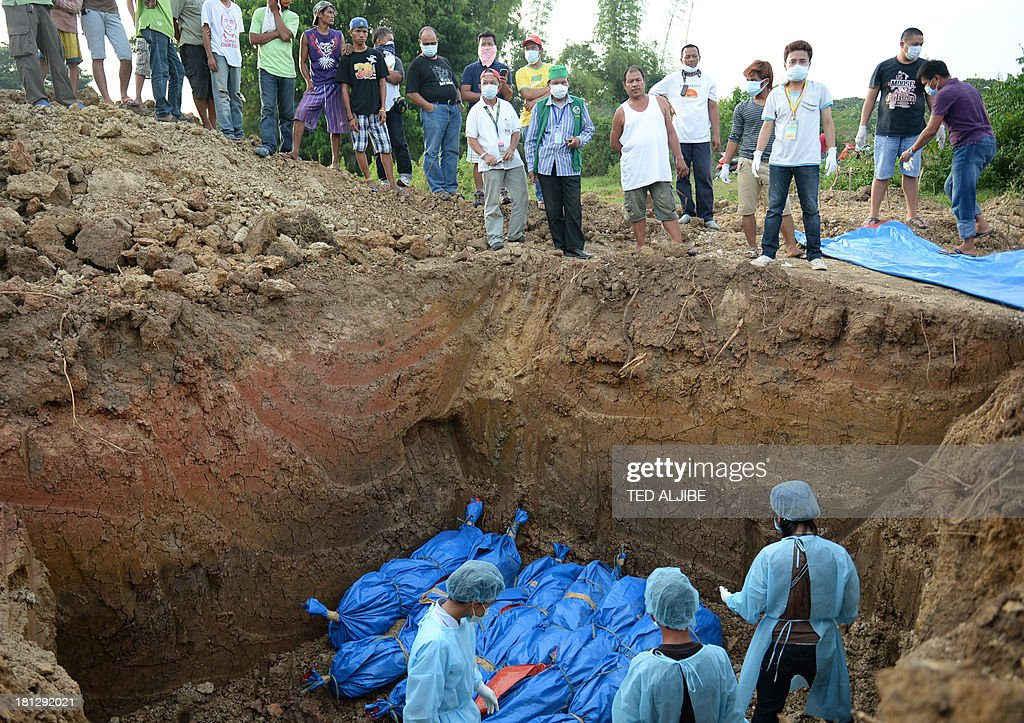 Volunteers bury the bodies of suspected Muslim rebels killed in the stand-off between Philippine government forces and members of Moro National Liberation Front (MNLF) during a burial on the outskirts of Zamboanga, on the southern island of Mindanao on September 20, 2013. Philippine security forces killed eight Muslim rebels on September 20 as they hunted the remnants of a guerrilla force hiding in homes of the major city and believed to be holding hostages.
