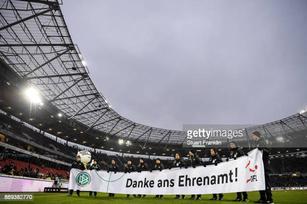 Volunteers carry a banner reading 'Thanks for the honorary post' prior during the Bundesliga match between Hannover 96 and TSG 1899 Hoffenheim at...