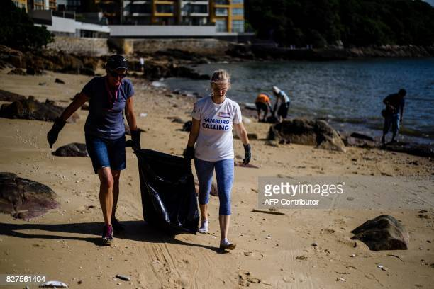 Volunteers carry a black bin bag as they help remove washed up palm oil from a beach on Hong Kong's outlying Lamma Island on August 8 2017 Residents...