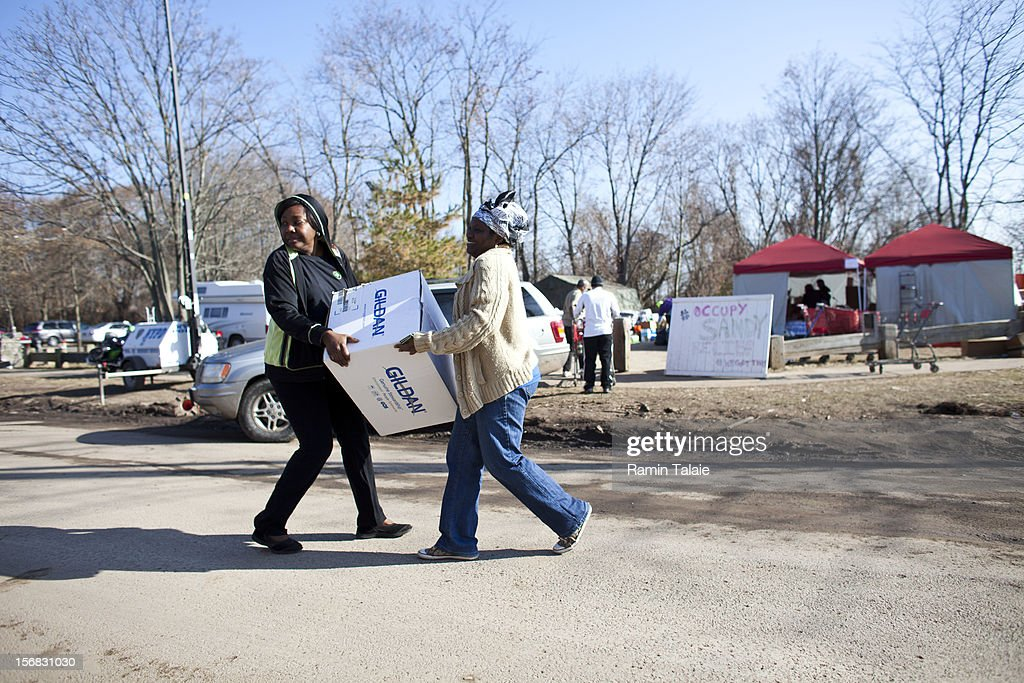 Volunteers carry a box of supplies at an Occupy Sandy distribution center to help victims of Superstorm Sandy on November 22, 2012 in the Staten Island borough of New York City. Sections of Staten Island were hard hit by flooding from Superstorm Sandy.