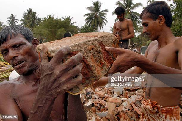 Volunteers carry broken bricks of a house as they start cleaning the coastal area destroyed by the tsunami January 9 2005 in Matara Sri Lanka...