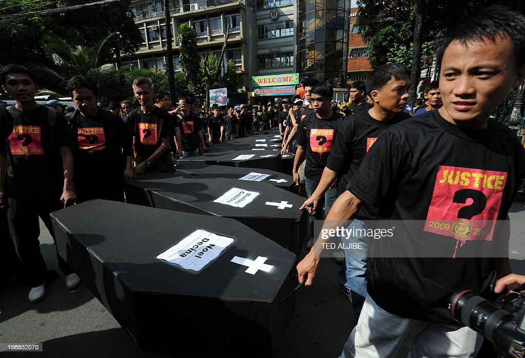 Volunteers carry mock coffins as they march towards Malacanang Palace in Manila on November 23, 2012, to commemorate the third anniversary of the November 23 Maguindanao massacre. Dozens of members of a clan whose leaders are on trial for the Philippines' worst political massacre are candidates in 2013 elections, some for the president's party, media and rights groups said November 23. The revelations sparked outrage on the three-year anniversary of the massacre, in which 58 people died, with critics saying the Ampatuan family's enduring political influence underlined the country's 'culture of impunity'.