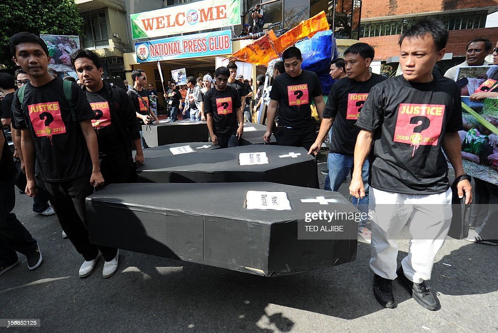 Volunteers carry mock coffins as they march towards Malacanang Palace in Manila on November 23, 2012, to commemorate the third anniversary of the November 23 Maguindanao massacre. Dozens of members of a clan whose leaders are on trial for the Philippines' worst political massacre are candidates in 2013 elections, some for the president's party, media and rights groups said November 23. The revelations sparked outrage on the three-year anniversary of the massacre, in which 58 people died, with critics saying the Ampatuan family's enduring political influence underlined the country's 'culture of impunity'. AFP PHOTO/TED ALJIBE