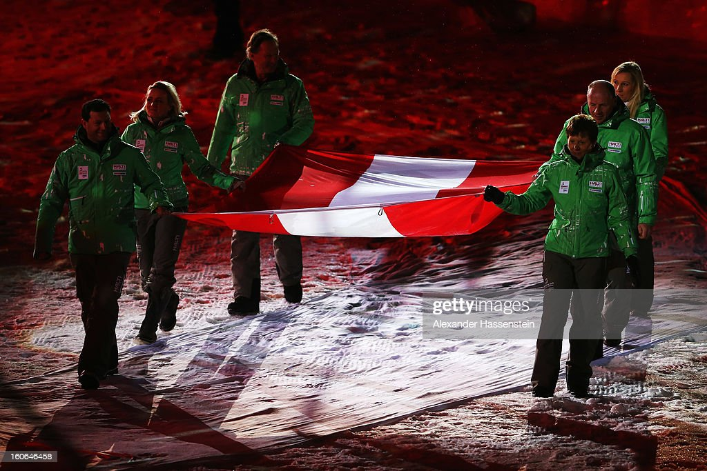 Volunteers carry the Austrian national flag into the arrival area during the opening ceremony for the Alpine FIS Ski World Championships on February 4, 2013 in Schladming, Austria.