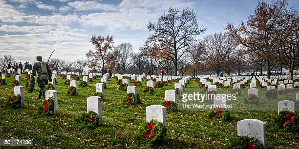 Volunteers carry wreaths in search of unadorned gravesite during as they participate in Wreath Across America to lay wreaths on each grave in...