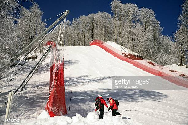 Volunteers check one of the Men's Downhill slope jumps at the Rosa Khutor Alpine center in the mountain cluster on February 2 2014 prior to the start...