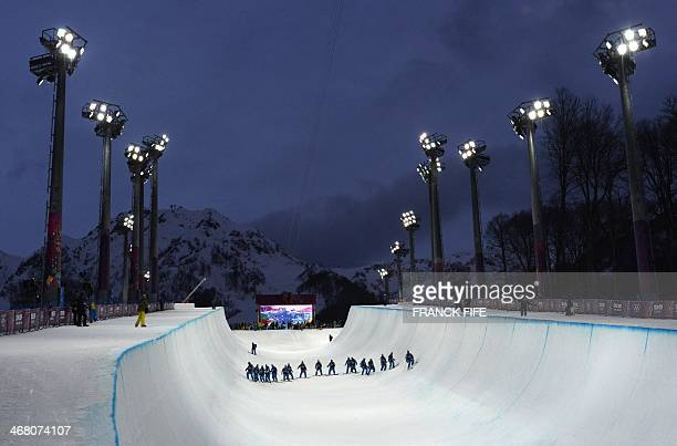 Volunteers check the condition of the half pipe before a Men's Snowboard Halfpipe training session at the Rosa Khutor Extreme Park during the Sochi...