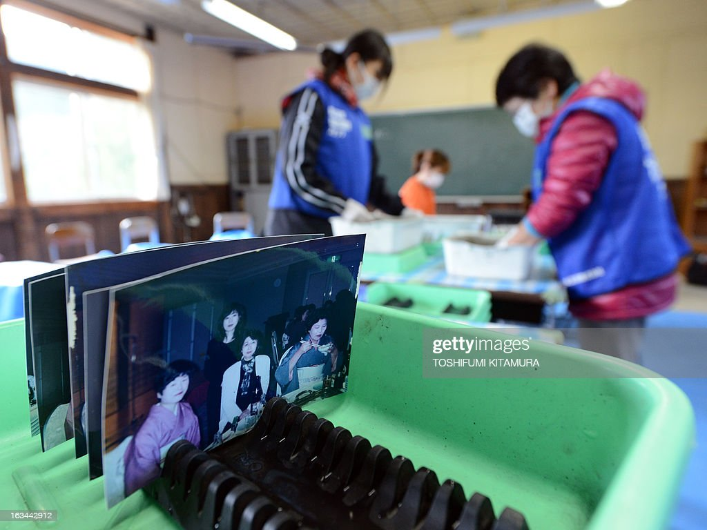 Volunteers clean pictures found in debris of the March 11 earthquake and tsunami disasters at the Tsukidate elementary school in Kesennuma, Miyagi prefecture on March 10, 2013. March 11, 2013 marks the second anniversary of the 9.0 magnitude earthquake that sent a huge wall of water into the coast of the Tohoku region, splintering whole communities, ruining swathes of prime farmland and killing nearly 19,000 people.
