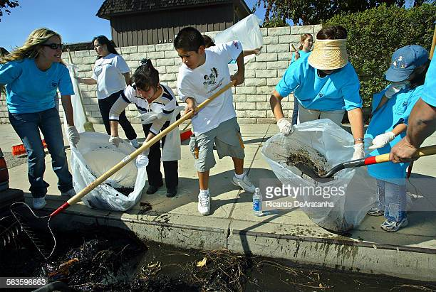Volunteers cleaning up trash from the gutter on Sepulveda Blvd during Make a Difference Day celebrated nationwide as a day to help others and beatify...