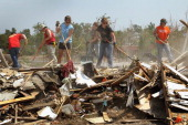 Volunteers clear debris from a home destroyed by the May 22 tornado July 29 2011 in Joplin Missouri The city continues with its recovery efforts...