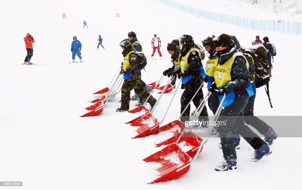 Volunteers clear snow from the course before the start of the Downhill section of the Womens Combined Alpine Skiing competition on Day 8 of the 2006...