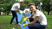 Volunteers collect litter, teenager smiling, environmental and ecological care