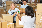 Volunteers Collecting Food Donations In Warehouse Smiling