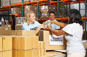 Volunteers Collecting Food Donations For Charity In Warehouse