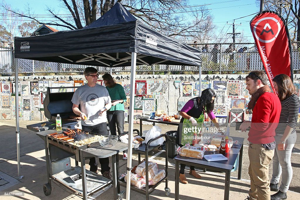 Volunteers cook sausages at a sausage sizzle as people vote in the national election at a polling station on July 2, 2016 in Melbourne, Australia. Voters head to the polls today to elect the 45th parliament of Australia.