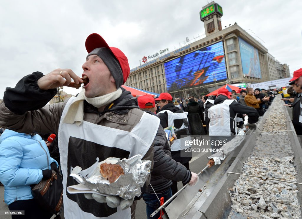 A volunteers cook tastes a piece of shashlyk, or skewered meat, which was cooked in a huge brazier in the Ukrainian capital of Kiev on March 2, 2013 to set a new world record. Officials of the Ukrainian National Register of Records fixed the new record for the longest shashlyk, a popular food item throughout the former Soviet Union, Eastern Europe, India, Iran, Mongolia, Morocco, Pakistan and Israel among other places, at 150.6 meters in length.