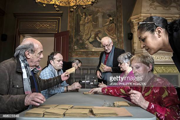 Volunteers count ballots after voting closed during the second round of the French departemental elections Valence eastern France on March 29 2015...