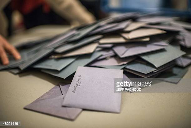 Volunteers count the ballots at the end of the first round of the French municipal elections on March 23 2014 at a polling station in Lyon AFP PHOTO...