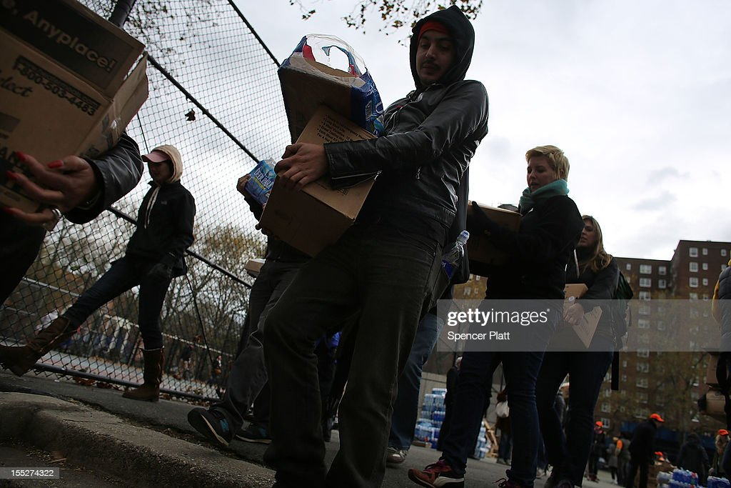 Volunteers deliver water and ready-to-eat meals to needy residents of the Red Hook Houses where they currently have no water or electricity due to Superstorm Sandy on November 2, 2012 in the Brooklyn borough of New York City. Limited public transit has returned to New York and most major bridges have reopened but will require three occupants in the vehicle to pass. With the death toll currently over 90 and millions of homes and businesses without power, the US east coast is attempting to recover from the effects of floods, fires and power outages brought on by Sandy.