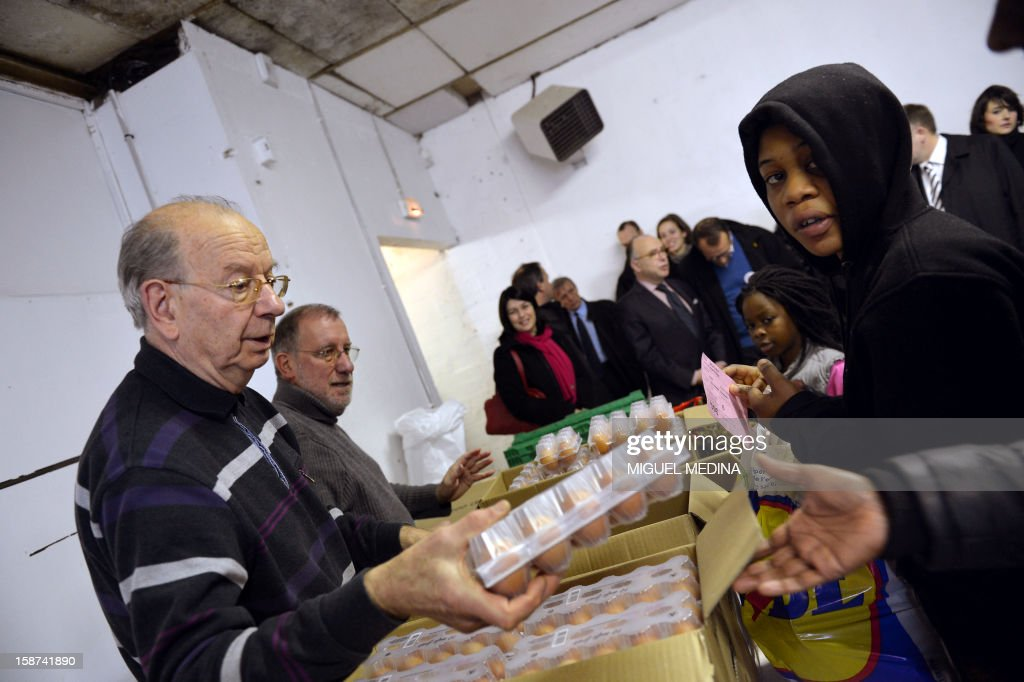 Volunteers distribute food at the French charitable organisation 'Les Restos du Coeur' (Restaurants of the Heart) on December 27, 2012 in Aulnay-sous-Bois, northern Paris. AFP PHOTO MIGUEL MEDINA