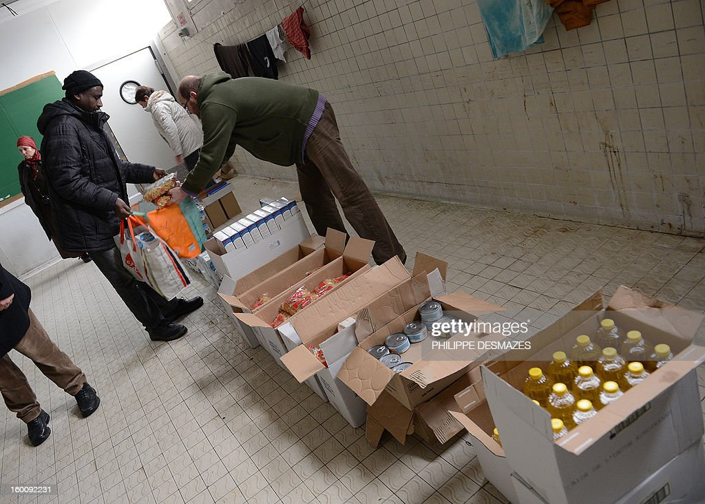 Volunteers distribute food to asylum seekers and refugees on January 18, 2013 in a former butcher shop in Dijon, eastern France. One hundred people, mainly men, from African and Eastern European countries live in this old industrial plant before its destruction at the end of winter.