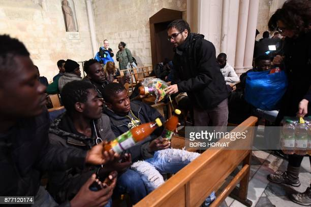Volunteers distribute food to migrants as they occupy the church of Saint Ferreol in Marseille on November 21 to protest against the life conditions...