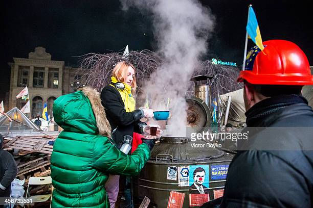Volunteers distribute hot tea to protesters on Maidan Square on December 14 2013 in Kiev Ukraine Antigovernment protests began three weeks ago when...
