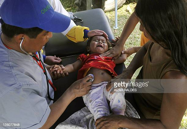 Volunteers doctors examine a little girl at the base camp set by indigenous Bolivians from the country's lowlying Amazon basin inlands marching...
