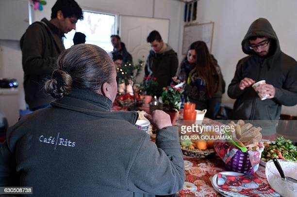 Volunteers eat a meal in the 'cafe Rits' in Ritsona refugee camp some 80 km north of Athens on December 21 2016 Before braving a 'trip of death' to...