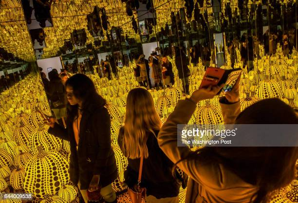 Volunteers experience the installation 'Infinity Mirrored RoomAll the Eternal Love I Have for the Pumpkins' as the Hirshhorn museum trains staff and...