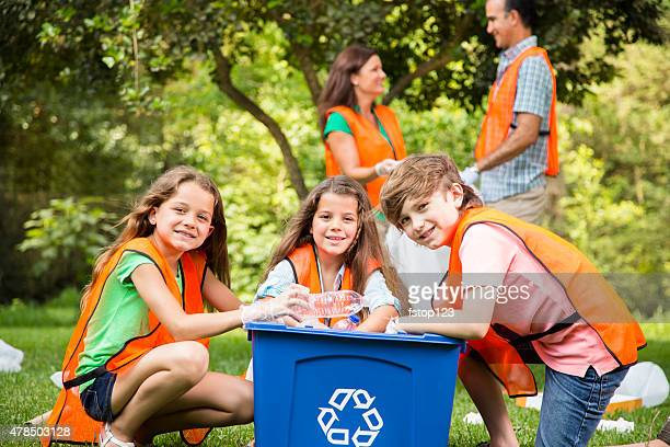 Volunteers: Family cleans up their community park. Recycling bin.