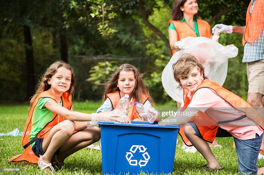 Volunteers: Family cleans up their community park. Recycling bin. : Stock Photo
