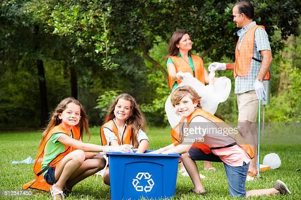Volontari: Famiglia clean up loro comunità park. Bidone per il riciclaggio.