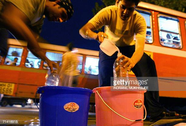 Volunteers fill drinking water for stranded bus commuters on a busy street in Mumbai 11 July 2006 after multiple bombs blast in local trains in the...