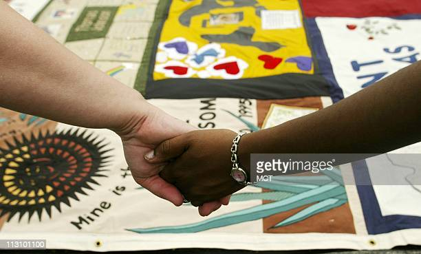 WASHINGTON DC Volunteers for the AIDS Memorial Quilt project hold hands as the names of the deceased are read on the Ellipse in Washington DC on...