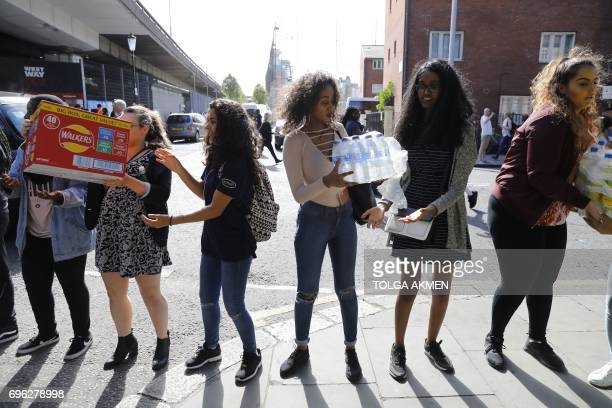 Volunteers form a human chain to ferry donations at an emmergency aid centre in west London on June 15 2017 Firefighters searched for bodies today in...