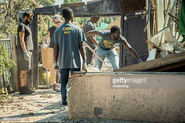 Volunteers from 'Centri Sociali Nord Est' and refugees help in clearing the damage caused by the tornado on July 10 2015 in Venice Italy One person...